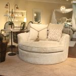 luxurious cream velvet round settee with large cushion design upon cream area rug aside cone wooden side table beneath vintage floor lamp in living room