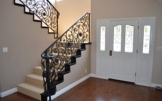 luxurious metal stairway railing wood floors a front door with sidelight feature
