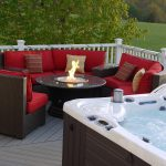 luxurious patio furniture in red color with round table and a round fire pit in its center an outdoor warm tub
