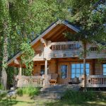 luxurious rustic cabin in the woods with large wood stairs and second floor construction front deck with furniture