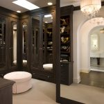 luxurious walk in closet design with large wooden closet with mirror and round puff on the cream floor with chandelier and floor to ceiling wooden framed mirror