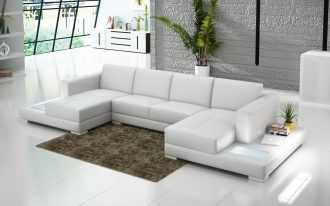 luxurious white double chaise sectional design with brown area rug on white floor with side stoage and decorative plant beneath grey brock wall with transparent glass window