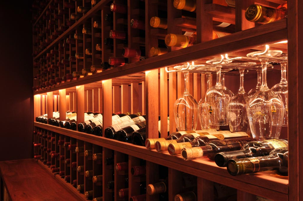 luxurious wooden wine cellar design with large plot and royal wine glasses inside the rack upon red flooring idea