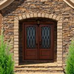 magnificent front door design with artistic detail double wood and fiberglass panel and beautiful granite wall and plants