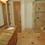 master bath remodel with bath tub and walk in shower plus wooden vanity units with natural granite countertop plus large mirrors