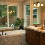 master bath remodel with bathtubs plus wooden vanity units with double sinks and decorative vase and candle holder and beautiful lighting and windows