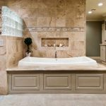 master bath remodel with large bathtub area and vanity units plus walk in shower and natural floor tiles and cool wall