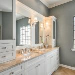 master bathroom remodel with white wooden bathroom vanitiy units with double sinks and mirror plus beautiful wall scones and crystal glass windows