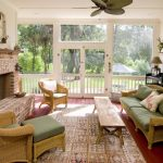 medium size sunroom with a comfy sofa with green mattress and decorative pillow a long wood table looks like a long wood bench a pair of rattan chairs with table a big basket bricks fireplace