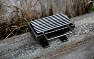 micro home hibachi grill with single front handle and black frame design upon rustic board aside grass in outdoor space