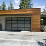 mid century modern garage doors with glass material combined with gray wall and wood wall plus plant and concrete floor