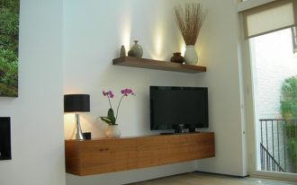 minimalist floating wood media console with TV set a porcelain vase for beautiful flowers a table lamp floating wood shelf for decorative items