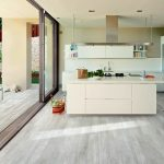 minimalist open plan kitchen design with white washed wood floors and white island and cabinetry and sliding glass door