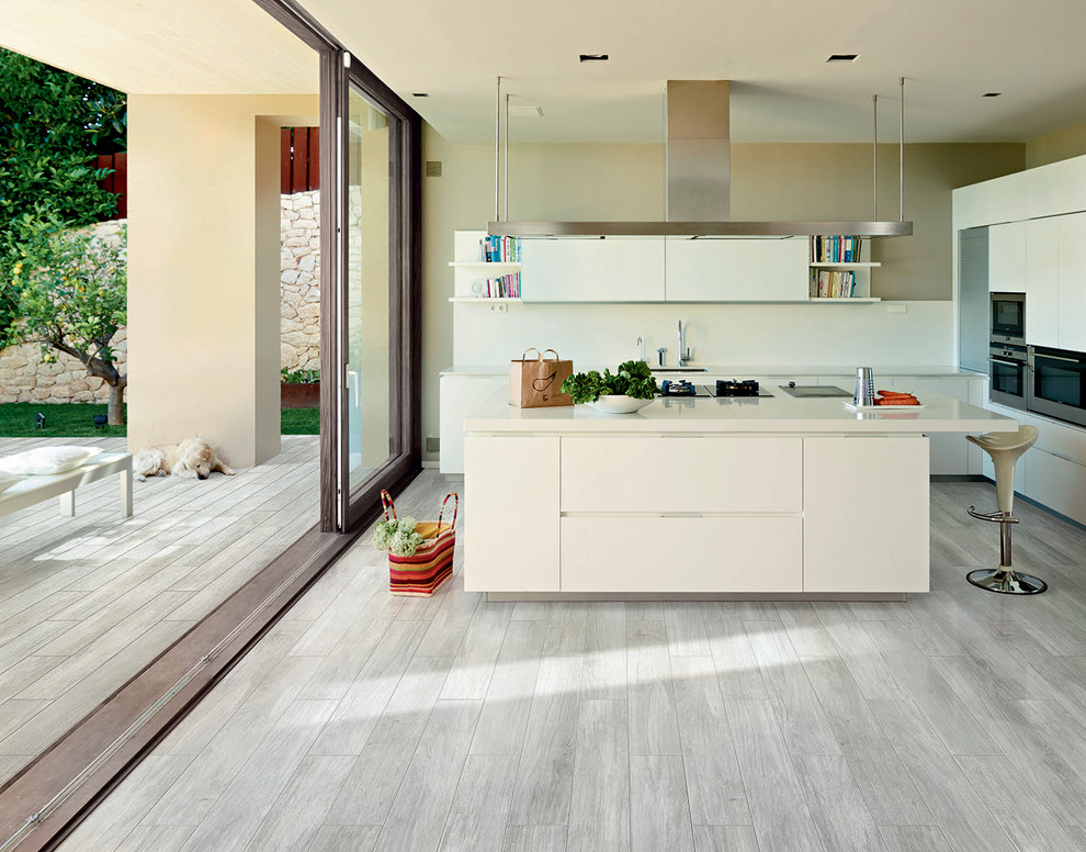 minimalist open plan kitchen design with white washed wood floors and white island and cabinetry and