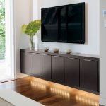 modern and minimalist floating media console in dark and shiny wood staining a wall mount TV set a large glasss vase and green plant as the decoration