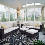 modern black patterned area rug beneath black rattan seating with white bolster in white sun porch design with cream curtain