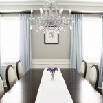 modern crystal funky cahndelier above flashing white table cloth on glosssy table with round backrested chairs with double windows with blue curtain