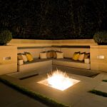 modern in ground fire pit design in rectangle shape before cream bench with stunning cushions and shrub decoration on the concrete patio