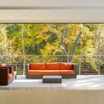 Modern Interior And Semi Outdoor Porch Design Separated By Folding La Cantina Door A Set Of Outdoor Furniture In Orange Color