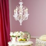 modern luxurious funky chandelier above white round table in pink room design with red curtain and flower vas aside bedding set