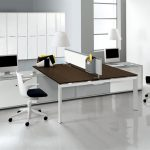 modern two sided desks design with short white partition and brown countertop and black and white swivel chairs and file storage and computer set