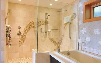 modern walk in shower with glass panel and no door a wall mounted shower heads natural river stones mosaic tiling for shower floors a corner bathtub with storage