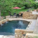natural look swimming pool with arch shape aside tall staircase beneath big trees and outdoor living space with black chairs and pink umbrella canopy