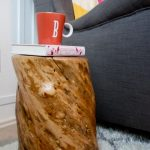 natural tree stump side table with natural brown tone color staining a book and a cup on top of table white fury mat dark black sofa