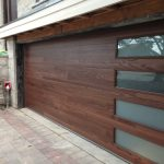 nice mid century modern garage doors with wood and glass windows plus natural brick wall and brick paver floor in basket weave pattern
