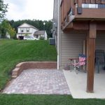 Patio Under Deck With Concrete Floor And Brick Paver Pattern Floor Plus American Chairs And Large Yard Area