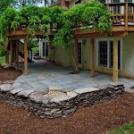patio under deck with natural stone floor and wooden pillar plus brick pattern wall and wonderful garden