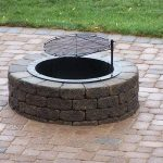 permanent in-ground fire pit in round shape plus grill for grilling the foods