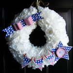 pure white fourth of july wreath design made of siphon roses with stars and beautiful ribbon of american flag