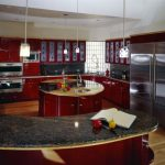 red curved kitchen island with granite countertop wooden cabinets plus pendant lighting and sink and wall oven and wooden floor
