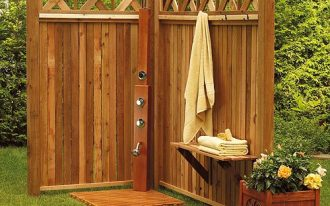rustic outdoor shower space with wall mount stainless steel shower head a planter box from wood some mounted hooks for hanging towel floating wood shelf for putting towel supplies
