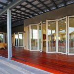 semi opened la cantina glass door with white trims semi red stained wood floors  a set of rattan furniture for porch