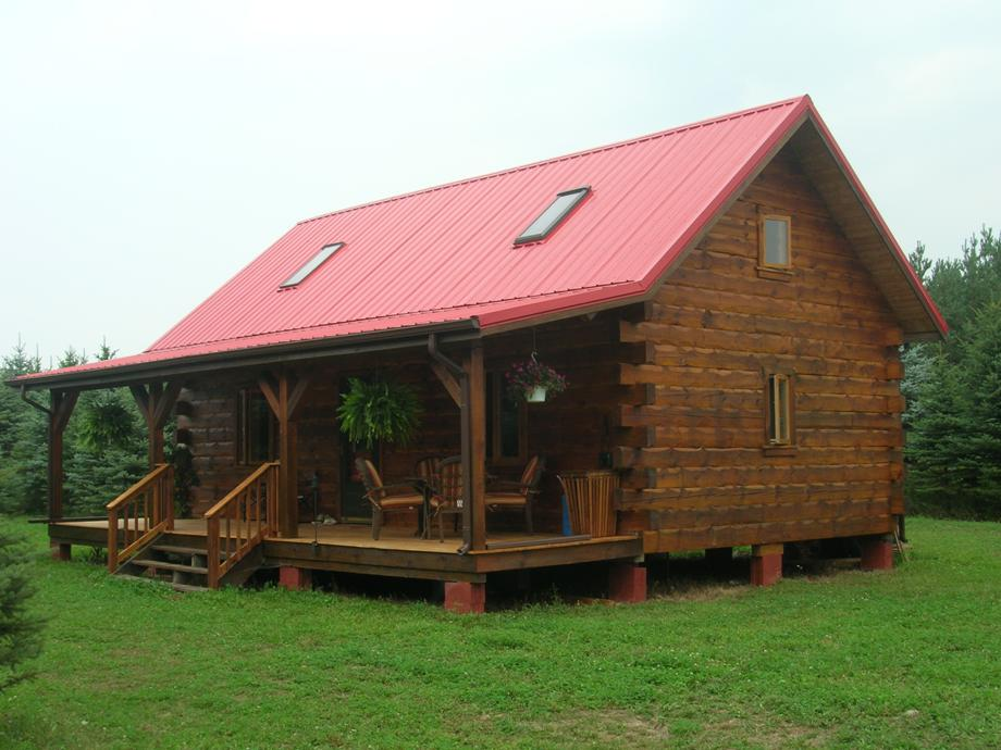 Semi Rustic Cabin With Porch And Wood Railing For Stairs In The Middle Of  Pine Woods