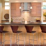 series 7 style of bar chairs in dark brown with metal legs metal surface kitchen island with sink and faucet  mosaic tiles kitchen backsplash wood top kitchen cabinets three units small pendant lights