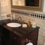 shabby chic tile backsplash mixed with elegant vanity cabinet with black countertop and white sink under framed mirror in modest bathroom best remodel