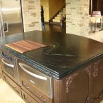 shiny black soapstone surface for kitchen island with storage and wood cut board
