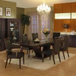 shiny bright funky chandelier in dining room with wooden rectangle table and tall leather backrested chairs above cream area rug aside wooden black storage design beneath photo gallery