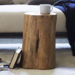 simple and natural side table made from tree stump cut a book a white cup for coffee or tea