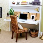 simple and small floating desk for working rattan chair with solid wood legs a laptop  a gold tone color standing lamp a rattan basket as storage