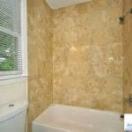 simple budget bathroom remodel with white window blind over flush combined with stylish white shower tub in brown tile wall