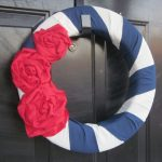 simple elegant blue white american wreath with red roses decoration hanging before black wooden door
