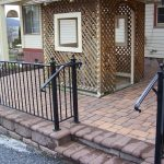 simple front terrace design with rustic pave patio and bamboo canopy and black rod iron railing fence
