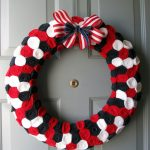 simple luxurious fourth of july wreath design made of round pillow with round black white and red flanel texture added with sweet ribbon of americal flag