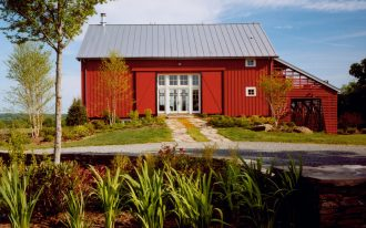 simple metal siding and roofing pole barn house with white glass door