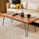 simple minimalist wood hairpin legs coffee table with dark-painted legs a cup of black coffee and a jug for black coffee refill light cream sofa with beautiful pillow soft white fury carpet