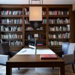 simple two sided desk in home library big and high book rack a lof of books collections
